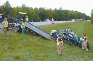PERSONNEL WORK to remove the vehicle involved in Sunday's accident on Interstate 295 in Bowdoinham. Traffic was reduced to one lane for about three hours.