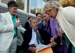 FORMER PRESIDENT GEORGE H.W. BUSH prepares to sign the marriage license of longtime friends Helen Thorgalsen, right, and Bonnie Clement, left, in Kennebunkport as officiant Nancy Sosa, third right, and Helen's daughter Lindsey, rear, look on in this Sept. 21 photo.