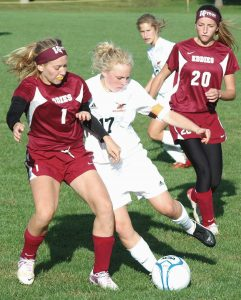 BRUNSWICK GIRLS SOCCER player Caley Nicholson (17) battles with Edward Little's Emily Schario (1), with Olivia Paione (20) close by during a KVAC contest at Brunswick on Tuesday. The Dragons won 2-1.