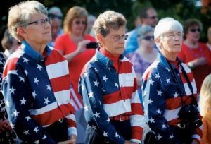 THE FREEPORT FLAG LADIES, from left, Elaine Greene, Carmen Footer and JoAnn Miller, listen at a ceremony Wednesday morning marking the anniversar y of Sept. 11, 2001, in Freeport.