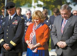 FROM RIGHT, GOV. PAUL LEPAGE, his wife, Ann and Maj. Gen. John W. Libby, former adjutant general of the Maine National Guard, bow their heads in prayer at a ceremony Wednesday morning marking the anniversary of Sept. 11, 2001, in Freeport.