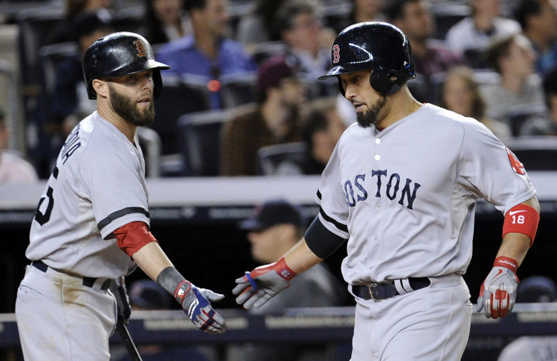 Shane Victorino of the Boston Red Sox, right, is welcomed by Dustin Pedroia after scoring in the fifth inning Thursday night. Boston went on to defeat the New York Yankees 9-8 in 10 innings.
