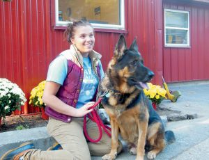 COASTAL HUMANE SOCIETY staffer Allie Athearn poses with Chisum prior to the canine's journey home to North Carolina on Friday.