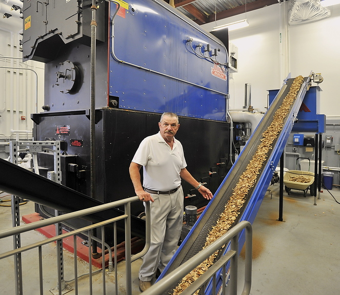 Topper West, maintenance, grounds and transportation director for Falmouth schools, shows the biomass furnace and conveyer belt filled with wood chips from Maine harvested wood. This is one of two and is located at the elementary school complex.