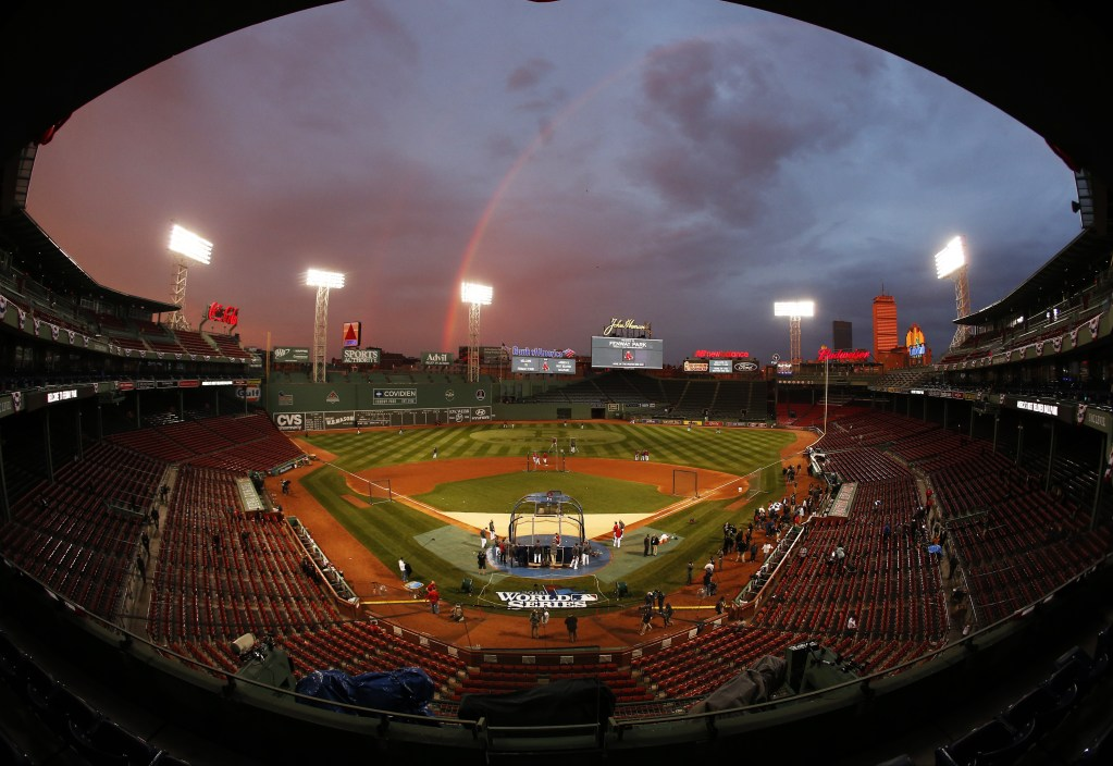 In this image taken with a fisheye lens, Boston Red Sox players take batting practice as a rainbow appears in the sky above Fenway Park Tuesday, Oct. 22, 2013, in Boston. With the Boston Red Sox back in the World Series, Wednesday's television ratings jumped for the opener.