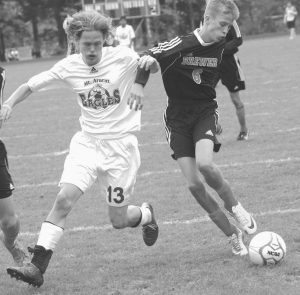 MT. ARARAT HIGH SCHOOL'S Ty Veno (13) battles with Brewer defender Carter Smith (6) for this loose ball during KVAC boys soccer action Saturday in Topsham.