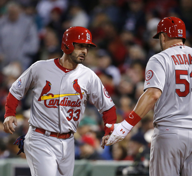 St. Louis Cardinals' Daniel Descalso (33) is congratulated by Matt Adams after scoring against the Boston Red Sox during the seventh inning of Game 2 of baseball's World Series Thursday, Oct. 24, 2013, in Boston. (AP Photo/Elise Amendola)
