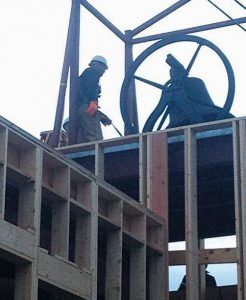 WORKERS HOIST a historic bell into place atop the new Unitarian Universalist Church of Brunswick at Pleasant and Middle streets this morning. The building under construction will replace a building that burned in June 2011. The bell's storied legacy includes surviving a church disaster in 1884 as well, when it came crashing through the steeple and roof during a fire at a previous church at the southeast corner of Maine and Mason streets.