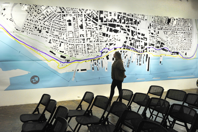 """Orianna Bailey, an intern at Space, studies a large map of Portland that is part of the gallery's exhibition """"Waterfront Visions 2050."""""""
