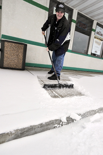 Bob Prevost, general manager of D'Angelo Sandwich Shop in North Windham, sweeps the first snow of the season from the entryway to his shop.