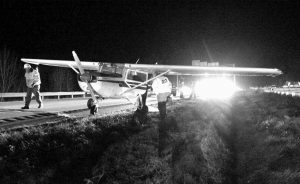 STATE POLICE and DOT officials look over a small plane that made a emergency landing in the southbound lane of Interstate 295 at mile 13 in Falmouth during evening rush hour traffic on Thursday. No injuries were reported.
