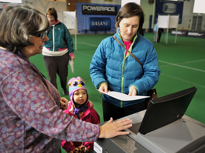 Erin Segal, 3, watches as an election clerk helps Erin's mother, Amy Segal, process her ballot at one of 500 new voting machines provided by the state to precincts with more than 1,000 voters. She was voting at the National Guard Armory on Stevens Avenue in Portland.