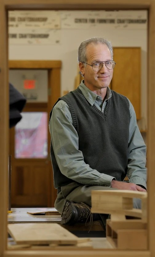 "Peter Korn, director of the Center for Furniture Craftsmanship, poses for a portrait in one of the school's classrooms. He came to Rockport in 1993, where he founded the center that has taught thousands of aspiring craftsmen the art of creating in wood. Korn's new book, below left, is ""Why We Make Things and Why It Matters: The Education of a Craftsman."" Below, Korn's dancing swan desk."