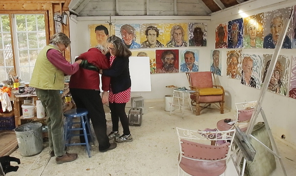 The artist's wife, Jill Hoy, right, and a studio assistant, Holley Mead, assist Jon Imber as he prepares to work in his Stonington studio, where evidence of his latest burst of creative energy decorates the walls. Hoy described her husband, who has had to relearn to paint after ALS robbed him of first his right arm, then his left, as one of the most courageous painters she's ever known. Since August, the artist has maintained a dizzying pace, creating more than 100 paintings.