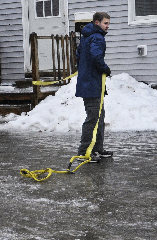 Antonio Sirabella holds on to a tow strap Sunday while attempting to walk through the parking lot of his Gardiner apartment building. More than a quarter-inch of ice coated tree branches and wires in the Augusta and Gardiner areas at noon.