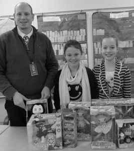 LISBON FIFTH-GRADE STUDENTS, Madison Ryder, center, and Emma Tapley, right, two of the newest junior volunteers at Lisbon Community School, offered assistance during recess to sort donations to the Maine Toys for Tots Campaign with Lisbon Community School Assistant Principal Ryan Patrie, left.