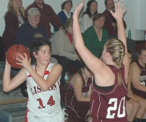 LISBON HIGH SCHOOL guard Jasmine Le (14) looks for someone to pass to while guarded by Monmouth's Jenna Davies (20).