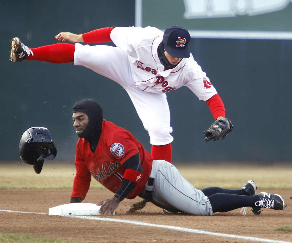 Sean Coyle of the Portland Sea Dogs tags out Corey Wimberly of the New Britain Rock Cats, who was attempting to go from second to third on a grounder to short in the first inning Thursday night. Portland won its home opener, 6-4.