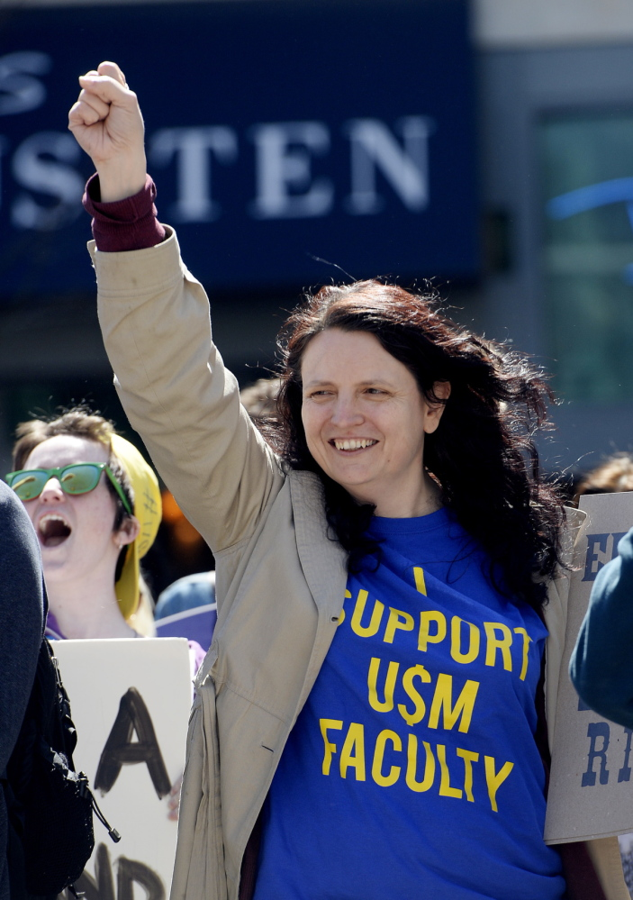 Michelle Kew, a USM graduate, shows her support for the school's faculty during the protest in Portland on Thursday