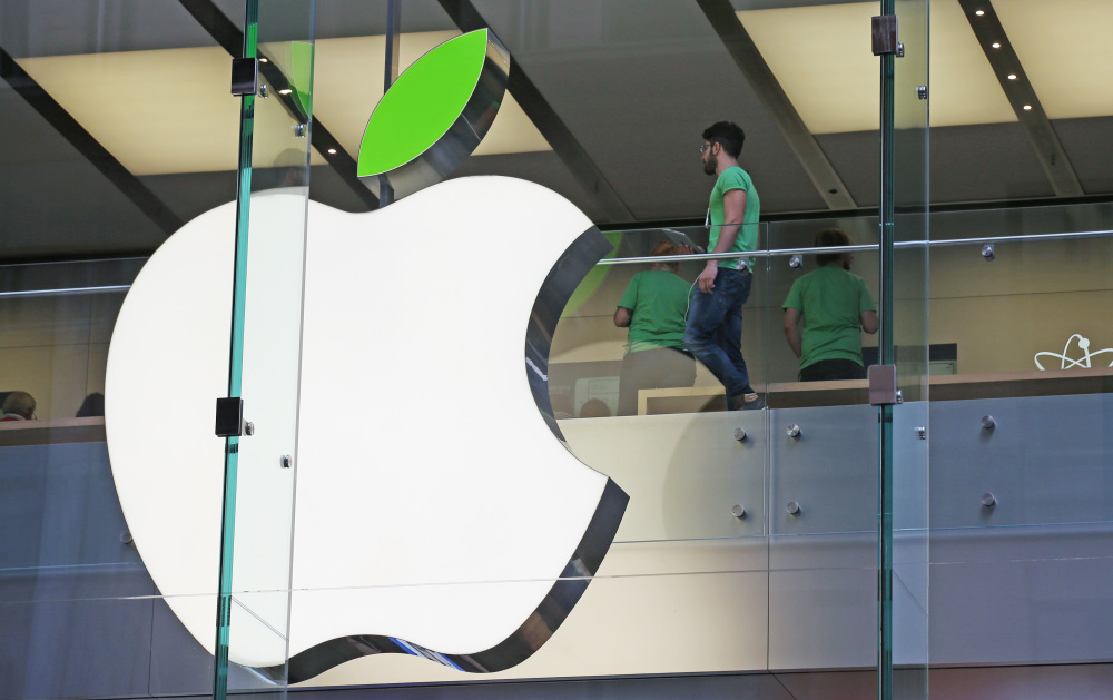 An Apple logo sports a green leaf at an Apple Store in Sydney, Australia, on Tuesday. Apple is offering free recycling of all its used products and vowing to power all of its stores, offices and data centers with renewable energy to reduce the pollution.