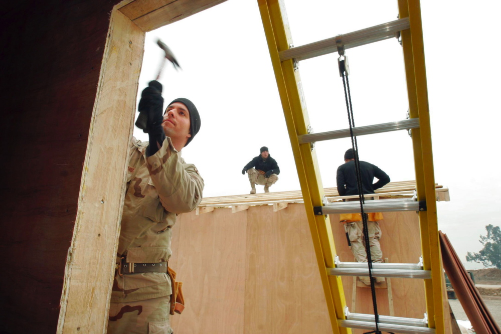 Sgt. Todd Kiilsgaard of Westbrook hammers a trim board on the front of a building that will be used by the Iraqi National Guard at a traffic control point near Mosul, Iraq, in 2004.