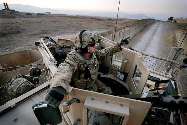 Sgt. Eric Crabtree of Hope, a gunner with the Convoy Escort Team of the 133rd Engineer Battalion of the Maine Army National Guard, rides in the gun turret on the way back from test firing his .50-caliber machine gun on the perimeter of Forward Operating Base Shank before departing on a convoy to Bagram Air Field in December.
