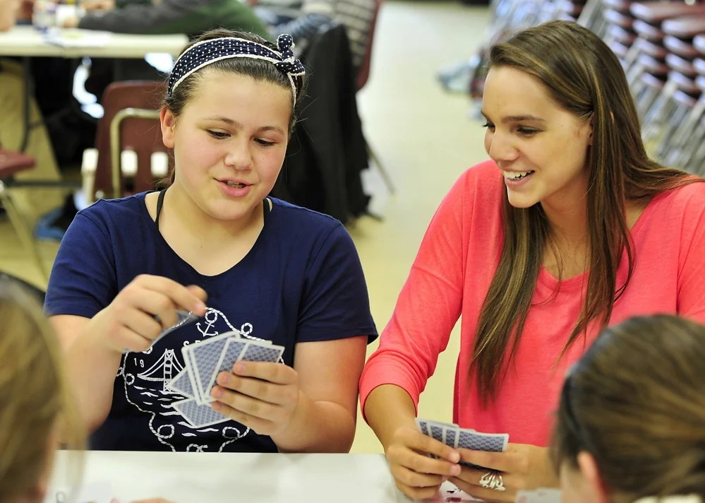 Westbrook High School sophomore Chelsea Rairdon, right, plays cards Wednesday with Abbigail Maxfield, 12, during a Big Brother-Big Sister session at the Westbrook Community Center. Rairdon is part of a student group trying to change attitudes about substance abuse at the school.