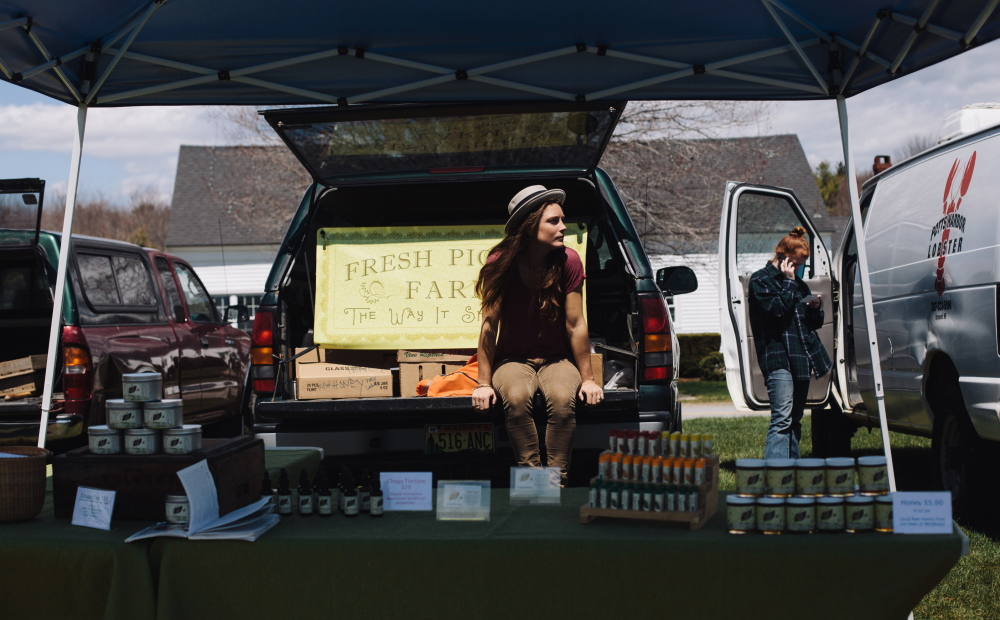 Crystal Ouimette of Fresh Pickins Farm in Limington and Windham takes in the afternoon sun during the opening weekend of the Crystal Springs Farmers Market in Brunswick this month.
