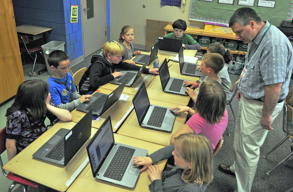 Tony Paine, CEO of Kepware Technologies, right, chats with students during a visit on Friday at Farrington Elementary School in Augusta. Paine's company donated laptops to the classroom earlier in the year. Staff photo by Joe Phelan