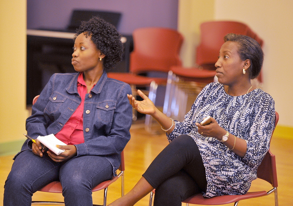 Ridelphine Katabesha, left, who immigrated from the Democratic Republic of the Congo, listens to Mia Ntahobari discuss the cutoff of state aid for some immigrants at a meeting of the Maine Immigrant Women's Network, which drew 20 women from a variety of Portland groups.