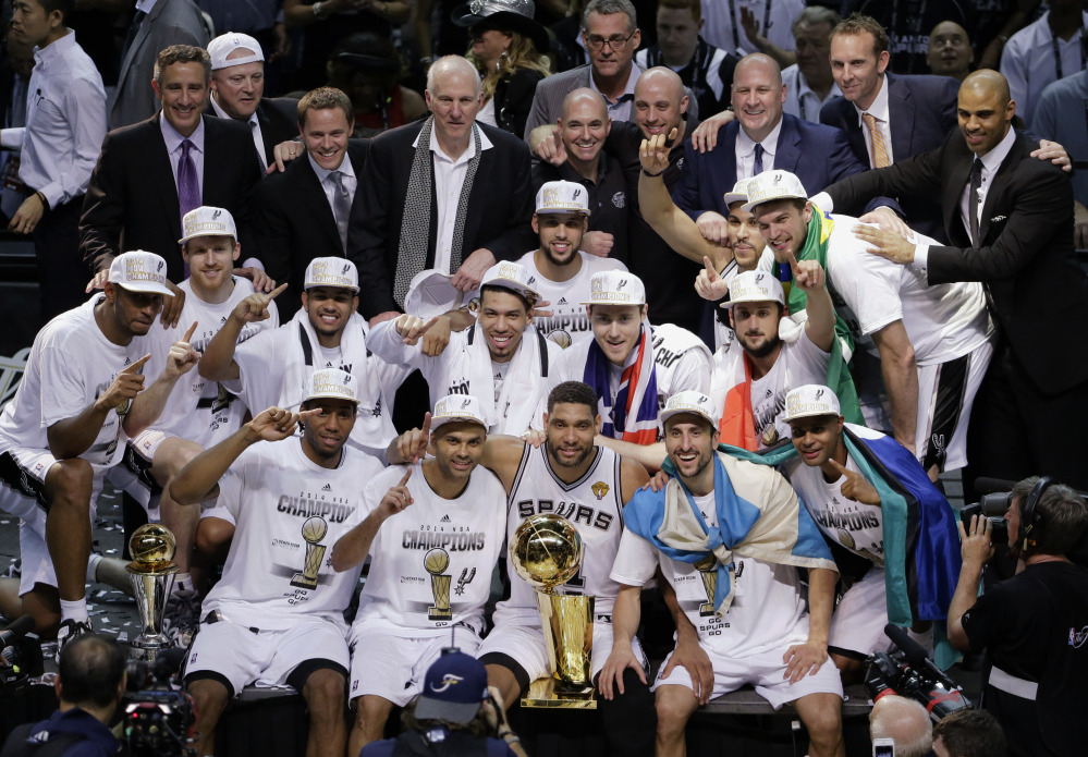 The San Antonio Spurs pose for a photo after Game 5 of the NBA basketball finals against the Miami Heat on Sunday, June 15, 2014, in San Antonio. The Spurs won the NBA championship 104-87.