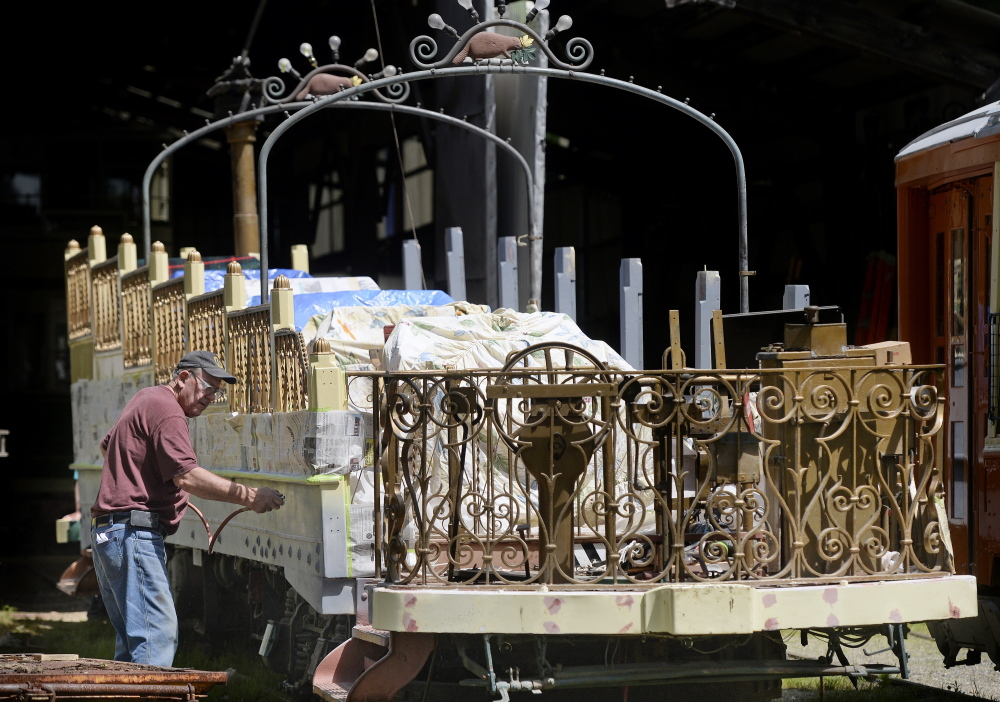 """Jim Mackell, a volunteer from Arundel, puts a coat of primer on the 1906 Montreal """"Golden Chariot"""" observation car at the Seashore Trolley Museum in Kennebunkport. The observation car will return to use during a July 5 celebration."""