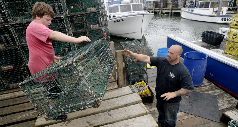 Rocco Mancini, 9, passes a lobster trap to his father, Nick Mancini of Falmouth, as they prepare for a trip to sea at Widgery Wharf in Portland. Last year, 125.9 million pounds of lobster were harvested in Maine.
