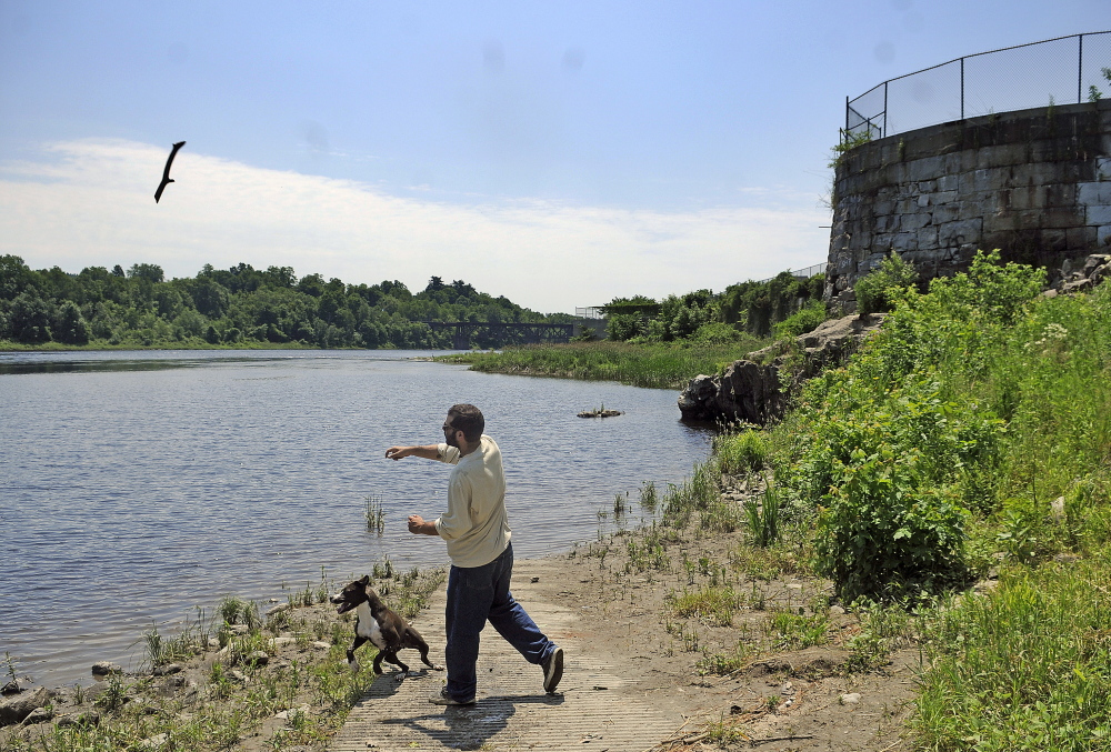 Mike Lehman of Windsor tosses a stick into the Kennebec River Monday for his dog at the site of the former Edwards Dam in Augusta.