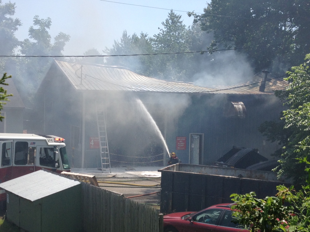 Firefighters work to extinguish a blaze Monday at R.P. Bell Collision in Saco.