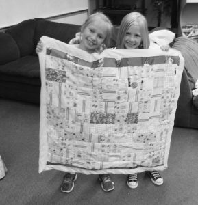 TWO GIRLS SHOW OFF A BABY QUILT made for MidCoast Hospital as part of the Williams Cone SACC program through Family Focus.
