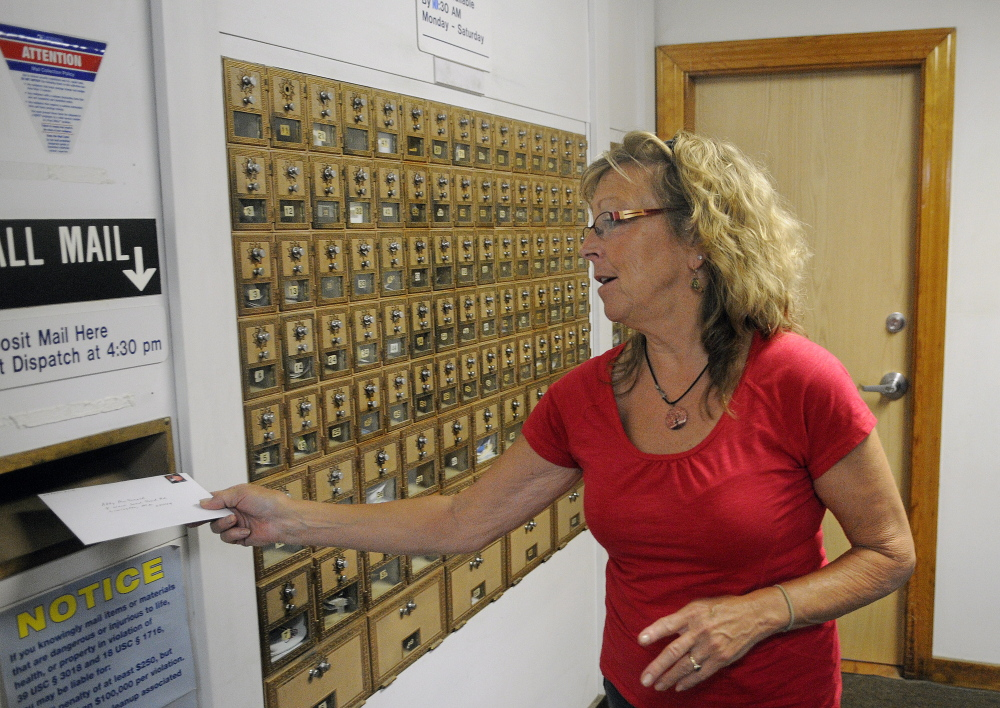 Anne Merrill mails a letter at the post office in North Monmouth in June. Cutting back the hours in North Monmouth and at many other rural Maine post offices is part of a nationwide effort to reduce costs for the financially troubled U.S. Postal Service.