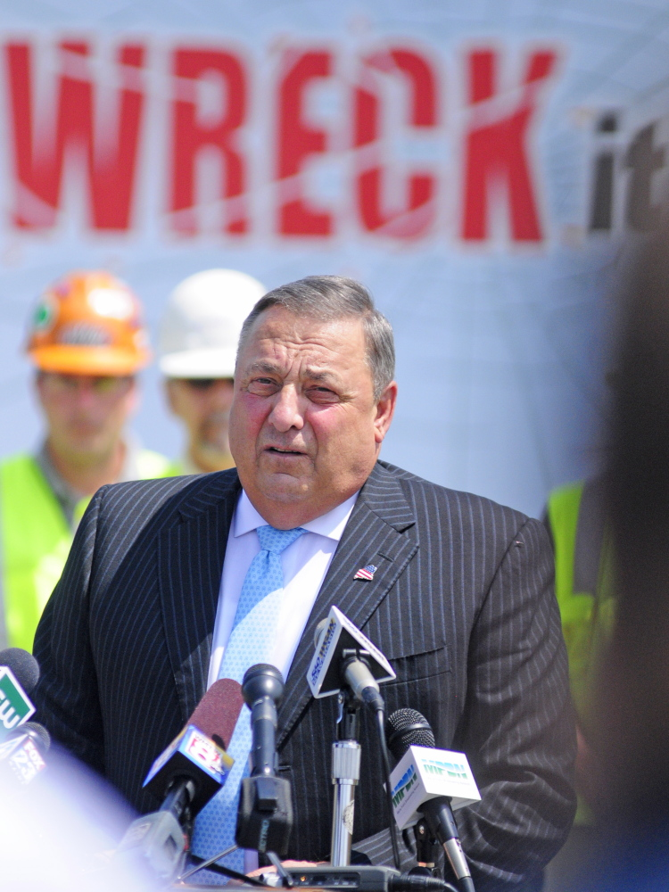 "Gov. Paul LePage stands in front of a truck with the words ""One text or call could wreck it all,"" as he talks about distracted driving on Tuesday during a news conference in the parking lot outside State Police headquarters in Augusta."