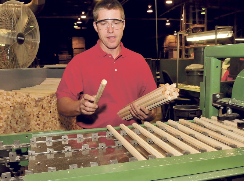 Pride Manufacturing company employee John Nelson places dowels on a machine that will mill them into Lincoln Log pieces at the Burnham company on Wednesday.