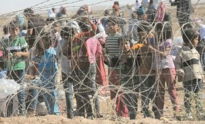 SEVERAL HUNDRED SYRIAN REFUGEES wait to cross into Turkey at the border in Suruc, Turkey, Sunday, Sept. 21.