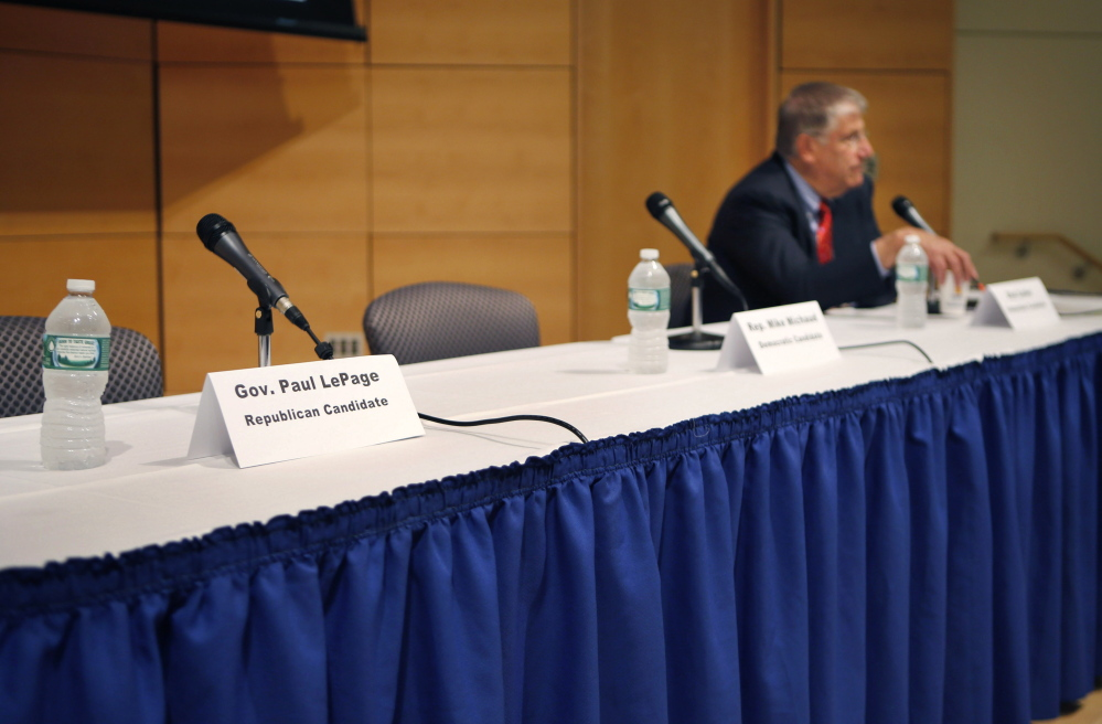 A seat at a table reserved for Gov. Paul LePage remains vacant after the governor decided to pull out of an energy forum at the University of Southern Maine in Portland on Friday. The Republican governor objected to the format for the event when he learned he would have to share the stage with the other gubernatorial candidates including independent Eliot Cutler, right.