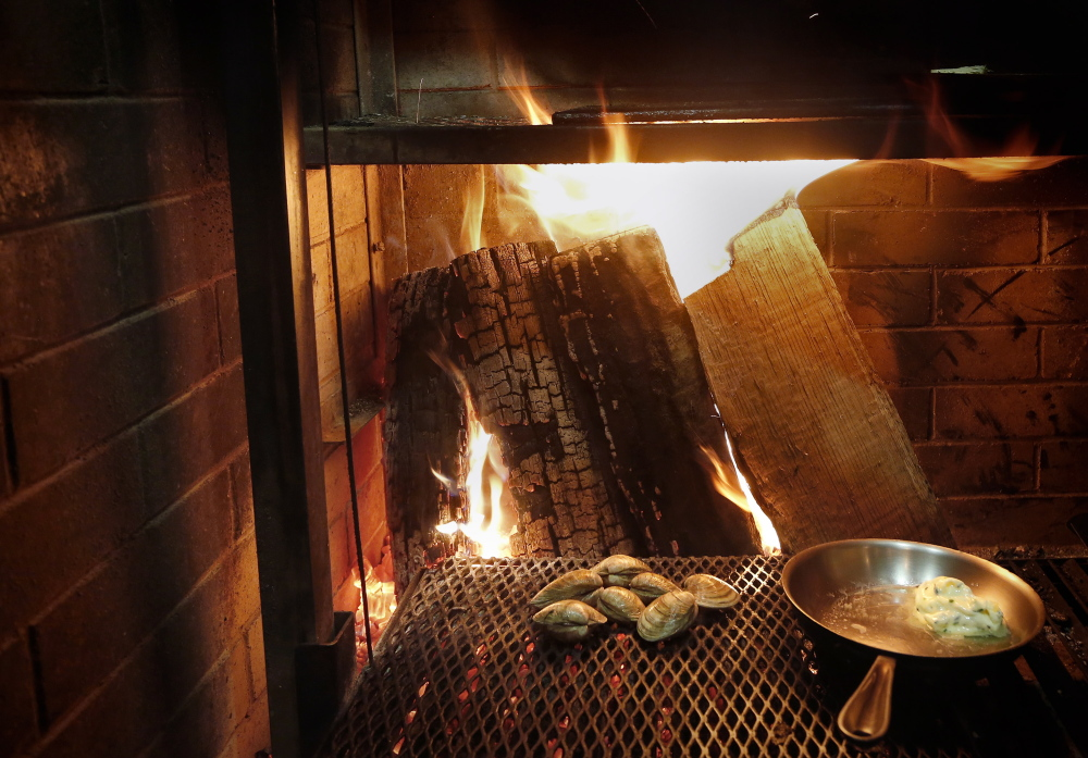 Clams roast by the fire of Lolita's custom wood grill.