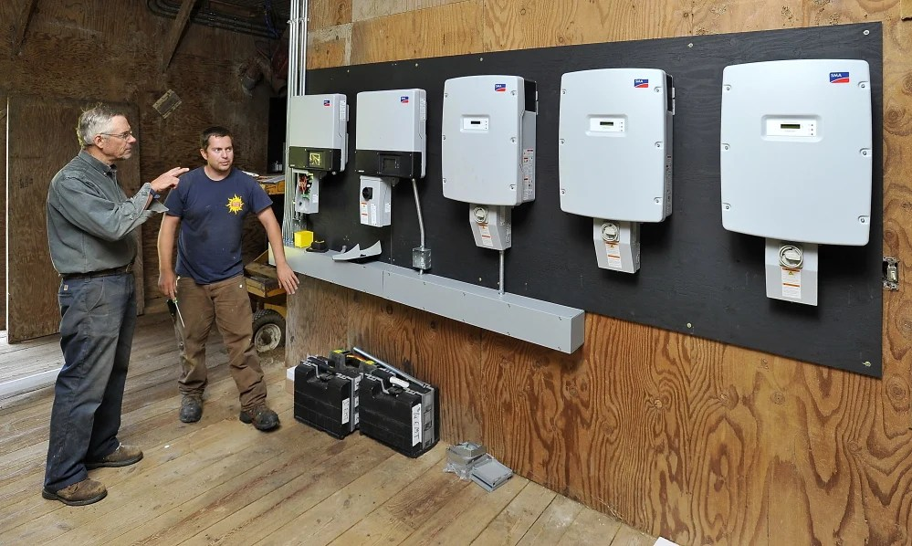 Russ Florenz of Sunnycroft Farm talks with ReVision Energy electrician Bill Levay as he installs inverters in a barn that will soon get 200 roof solar panels. ReVision Energy hopes it's the first of many community solar farms for people unable to install panels on their own properties.