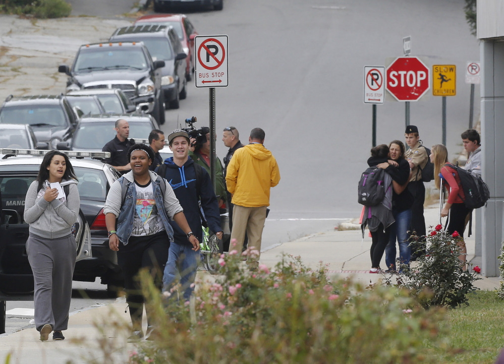 Students gather outside Manchester West High School after a 90-minute lockdown ended Thursday in Manchester, N.H. Police arrested Damian Johnson, 21, a former student, who showed up in a classroom with a pellet gun in his waistband.