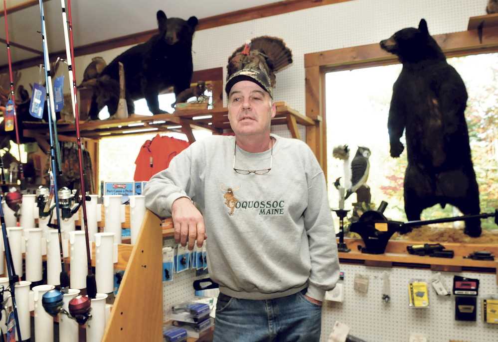 "Gerald White stands in his sporting goods store Rivers Edge Sports in Oquossoc surrounded by fishing gear and two stuffed black bears. White said a bear-baiting ban would have a devastating impact on his business and others that depend on the season. ""There is no question it would hurt business and we would never recover,"" White said."