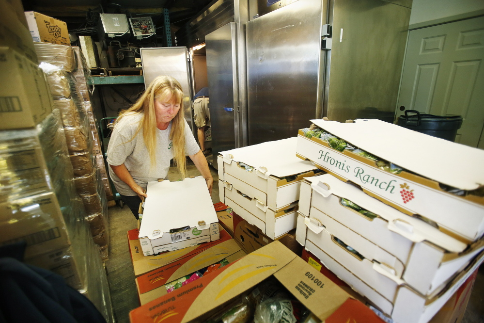 Jodi Bissonnette, director of York County Food Rescue in Alfred, unloads a carton of grapes from a pallet Monday at the group's warehouse in Alfred.