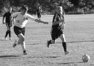 RICHMOND HIGH SCHOOL boys soccer player Brendan Emmons (14) and Pine Tree Academy's Frank Hodson (11) chase after a loose ball in a game at Freeport on Thursday. Richmond won, 2-0 to improve to 10-0.