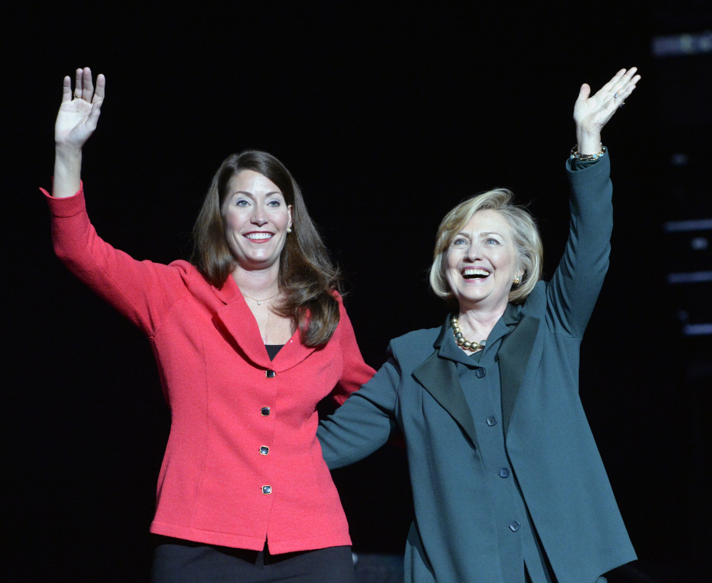 Kentucky democratic senatorial candidate Alison Lundergan Grimes, left, and former Secretary of State Hillary Clinton wave to a group of supporters during a rally in Highland Heights, Ky., Saturday, Nov. 1, 2014. (AP Photo/Timothy D. Easley)