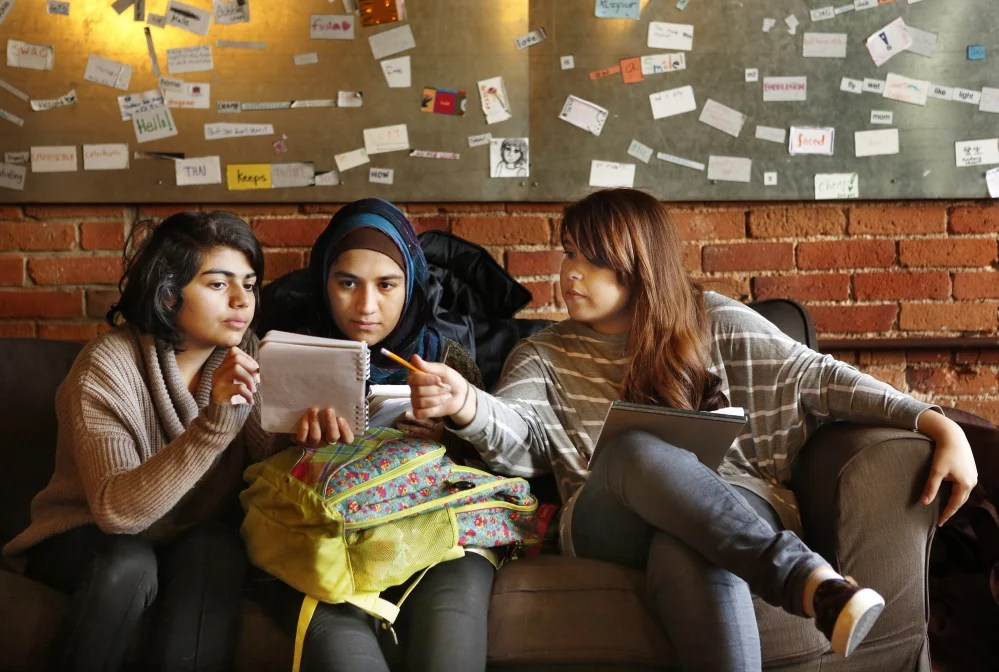 From left, Elahe Seddiqi, Maryam Abdullah and Mary Khadim look over a story that Seddiqi is working on at The Telling Room in Portland on Thursday. Seddiqi is a sophomore at Portland High School, Abdullah is a junior at Portland High and Khadim is a freshman at Deering High School. The Telling Room works with students in 50 schools in Maine.