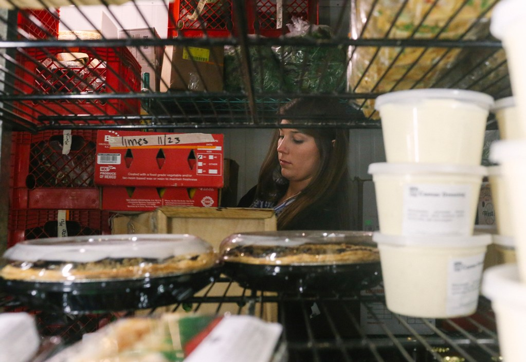 Ellis Linsmith grabs produce from the refrigerator at Rosemont Market and Bakery in Portland. insmith works at Rosemont between 15-20 hours per week while attending high school as a senior, and saves 75 percent of her earnings for college, which she hopes to graduate debt free.